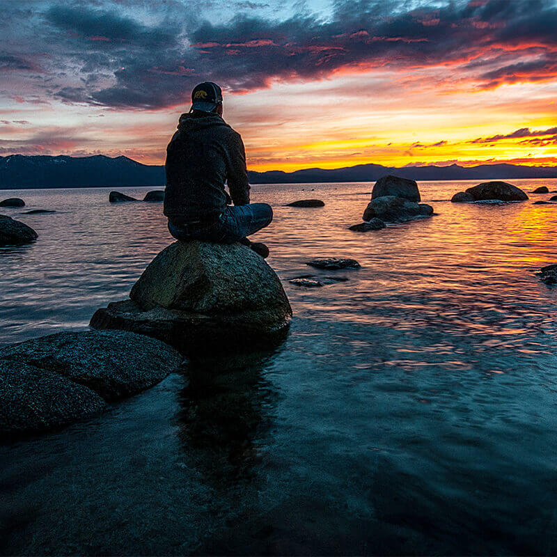 Photo of a man sitting by himself near a lake at sunset